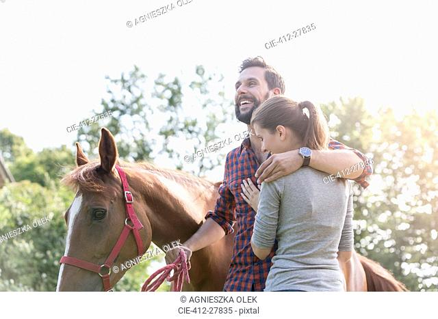 Smiling couple hugging near horse