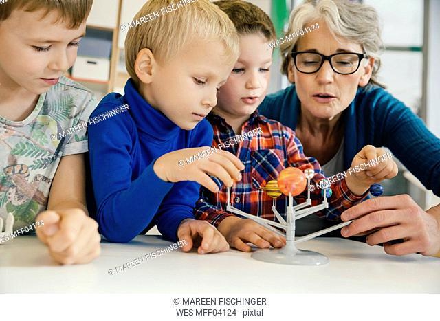 Pre-school teacher explaining solar system model to boys in kindergarten