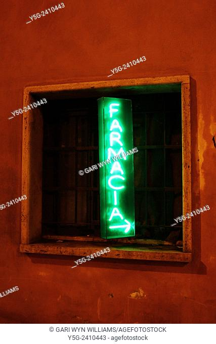 Green neon pharmacy sign at night in rome Italy