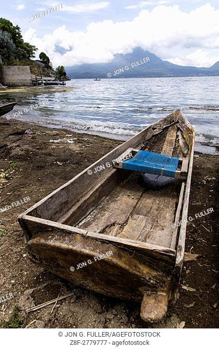 A cayuco or fishing boat on the shore of Lake Atitilan at San Antonio Palopó, Guatemala with Lake Atitlan and the San Pedro Volcano in the clouds