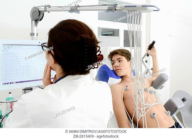 Cardiologist performs ECG,electrocardiogram on teenage boy