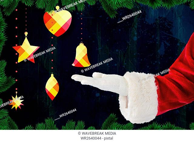 Santas hand pretending to hold a christmas bell against digitally generated background