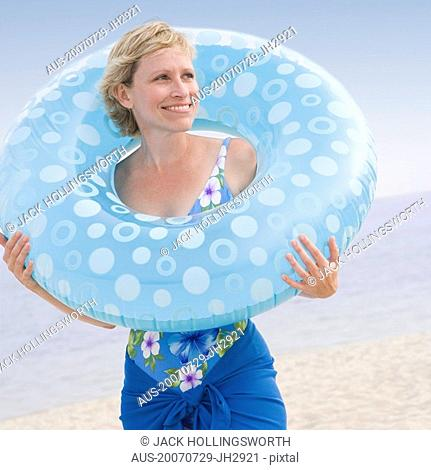 Mature woman holding an inflatable ring and smiling