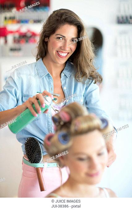 Portrait of confident hairdresser spraying hairspray in woman's hair at salon