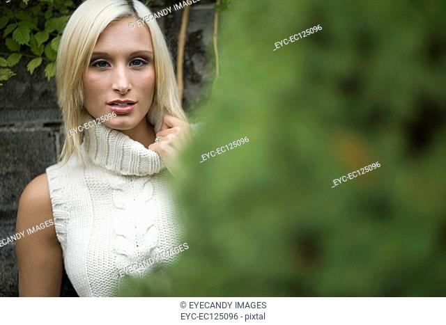 Portrait of young blonde woman standing in front of wall