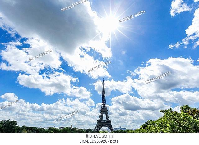 Sunbeams over distant Eiffel Tower, Paris, Ile de France, France