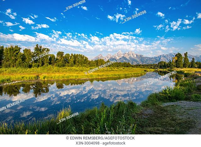 Still waters of the Snake River reflects Teton Mountain Race and cloudy skies, Grand Tetons National Park, Teton County, Wyoming. USA