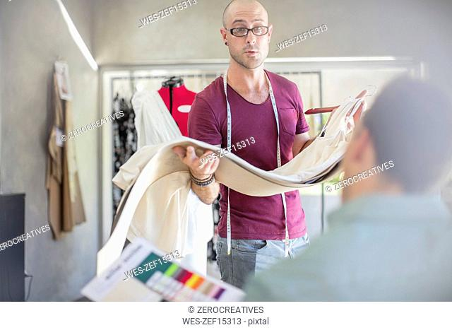 Fashion designer holding fabric in studio