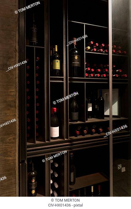 Wine bottles organized on wooden shelves in wine library