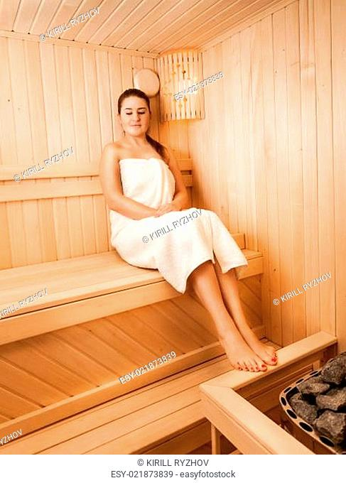 b40ad171cf Woman in towel sitting on bench at sauna next to oven