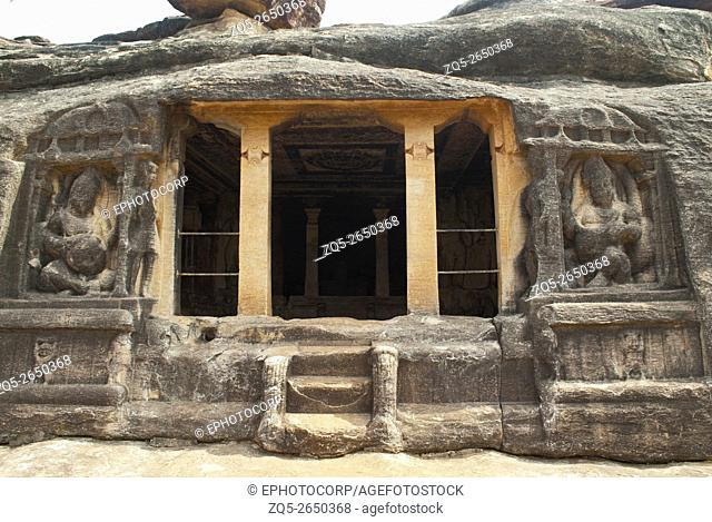 Front view of Ravanaphadi rock-cut temple, Aihole, Bagalkot, Karnataka, India. Two Kubera dwarpalas on the either side of the main entrance and a carved ceiling...