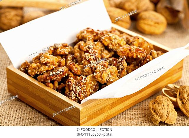 Sugared walnuts with sesame seeds in a wooden box