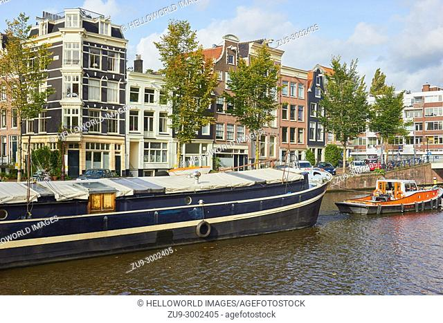 Tug boat guiding a barge along Nieuwe Herengracht canal, Amsterdam, Netherlands