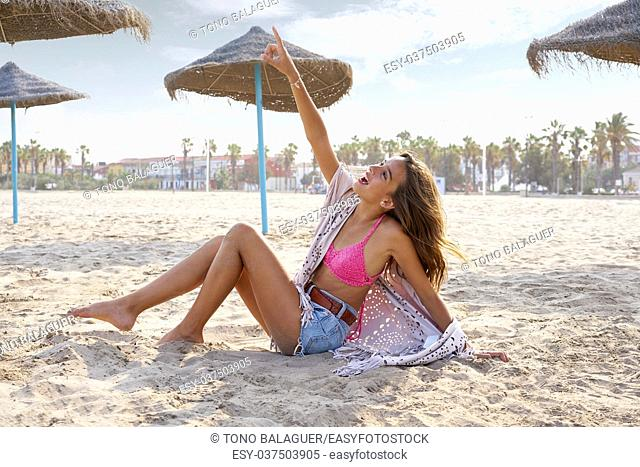 Teen girl on the beach happy pointing finger to sky near thatch umbrellas