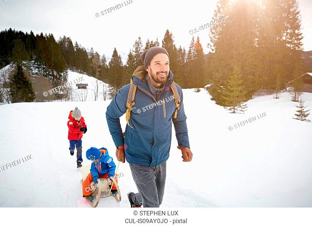 Young man pulling sons on toboggan in snow covered landscape, Elmau, Bavaria, Germany