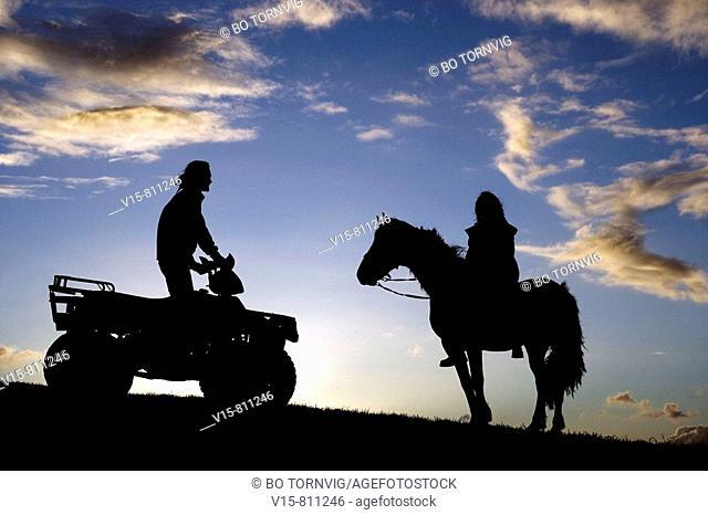 Quad bike and horse rider on ridge