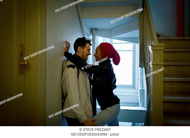 Young couple hugging in hallway