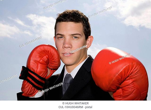 Man in business suit with boxing gloves