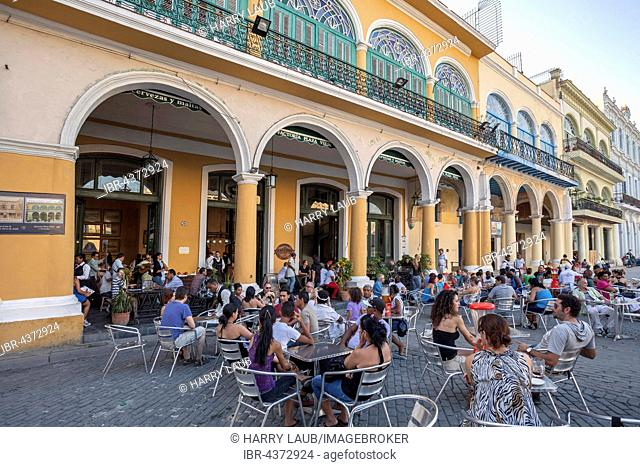 Guests sitting in front of a restaurant at the Plaza Vieja, Old Havana, Havana Vieja, Cuba