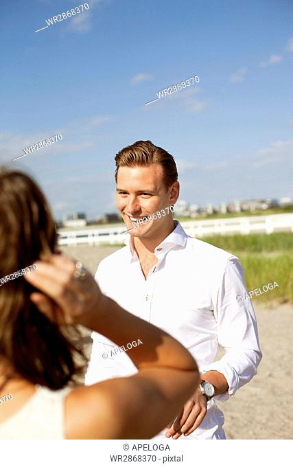 Smiling young man talking with female friend at beach