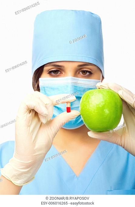 Doctor with green apple and pill isolated