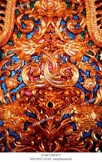the detail of ancient thai decorated pattern that include handcraft wood carving work,gold painting and decorated with gold plate,mirror and precious stone