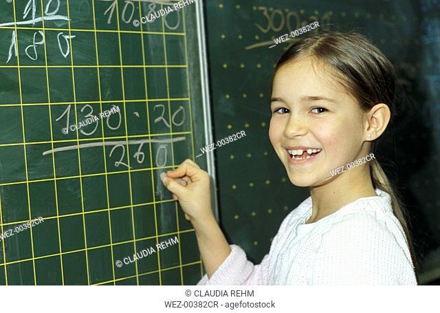 Girl writing on blackboard, portrait