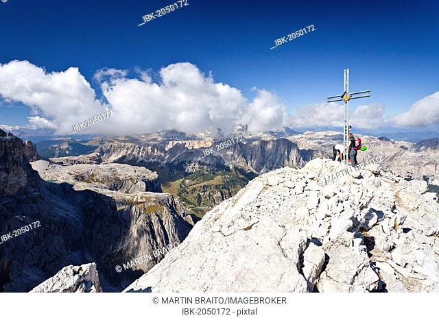 Climbers at the summit cross, Boeseekofel fixed rope route, Fanes and Heiligkreuzkofel ranges at back, Dolomites, Trentino, Italy, Europe