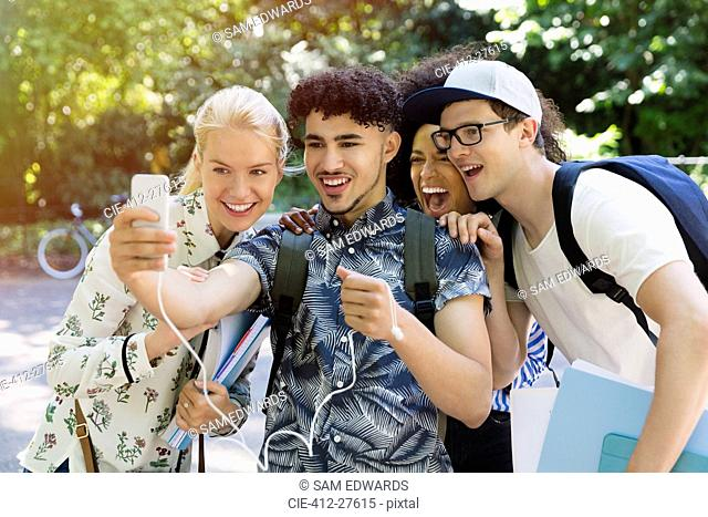 Friends taking selfie with camera phone in park