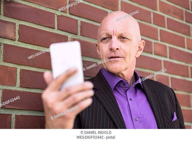Businessman at brick wall using cell phone