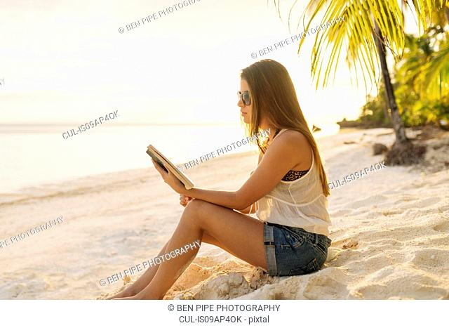 Young woman reading book on Anda beach, Bohol Province, Philippines