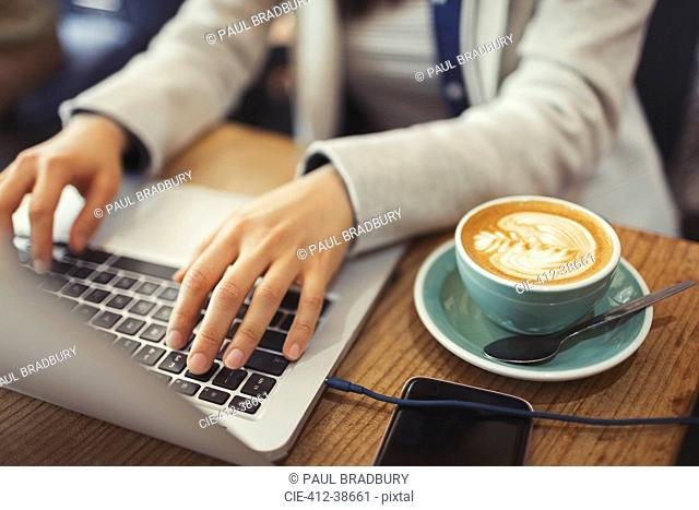 Hands of young woman using laptop, drinking cappuccino in cafe