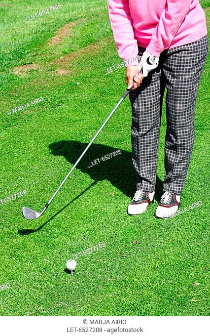 A golfer plays a golf ball with a golf club in a sand trap of the golf course  Finland