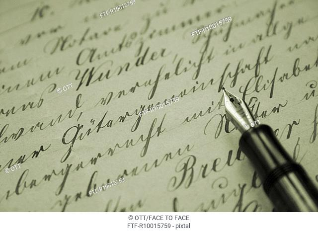 An ink pen is put on the paper which consists of cursive writings