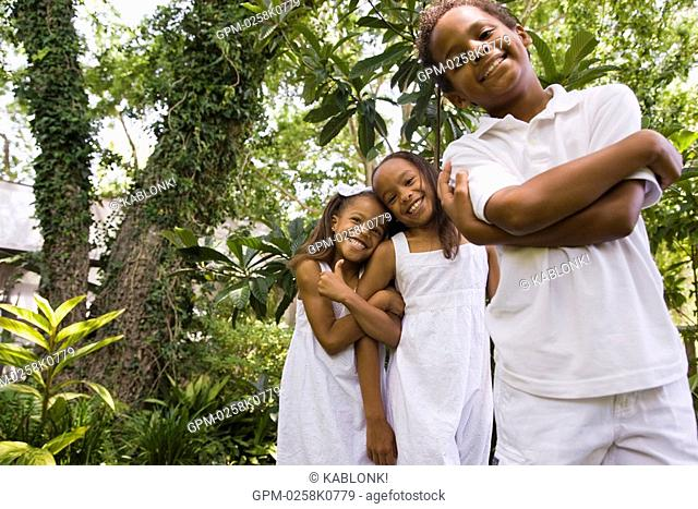 Portrait of happy elementary age African American children playfully posing in outside nature setting, low angle view