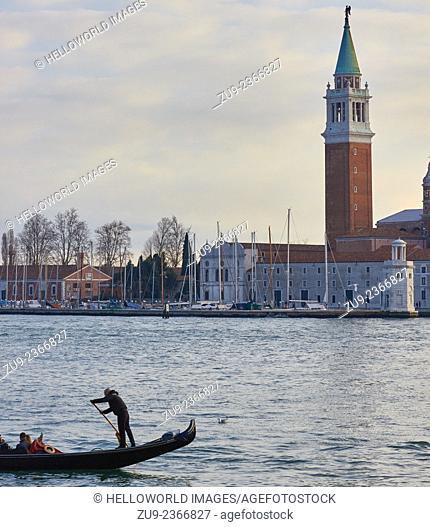 Gondolier rowing on Venice lagoon with island of San Giorgio Maggiore in background, Veneto, Italy, Europe