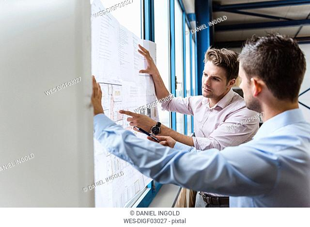 Business people standing t window, discussing production plans