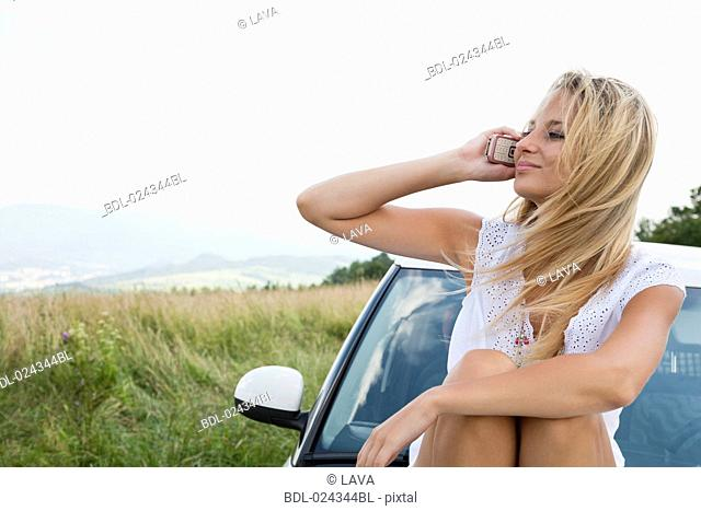 portrait of young woman siiting on bonnet of car talking on mobile phone
