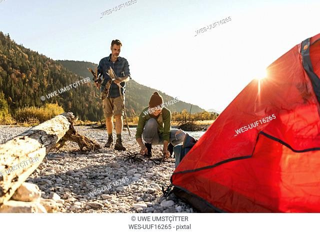 Mature couple camping at riverside, collecting wood for a camp fire