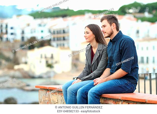 Pensive couple looking away sitting on a ledge on vacation in a coast town