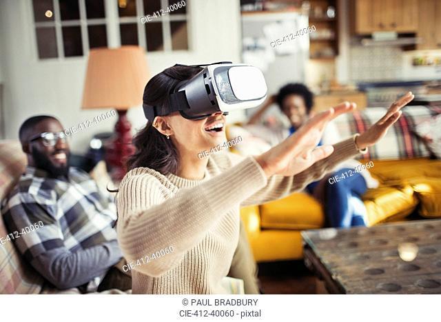 Woman gesturing, using virtual reality simulator glasses in living room