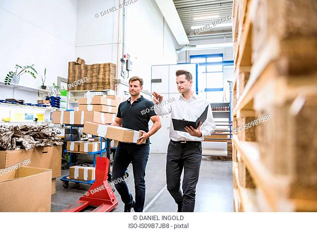 Warehouse worker carrying cardboard box for factory manager in warehouse