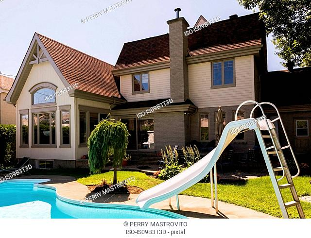 Rear view of a grey brick and cream cladding with grey trim cottage style home and landscaped backyard with in-ground swimming pool and slide in summer, Quebec