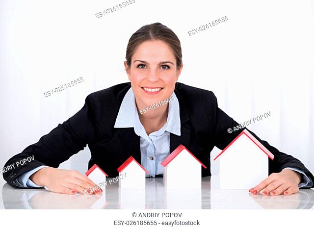 Portrait Of Happy Businesswoman With Different Size Of House Models At Desk