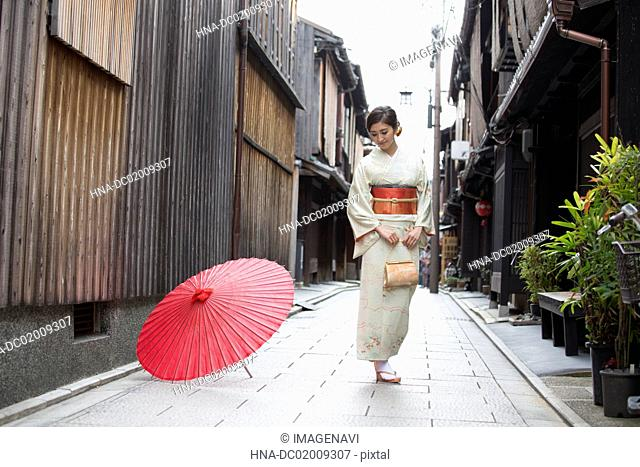 Young Japanese woman in kimono standing on the street