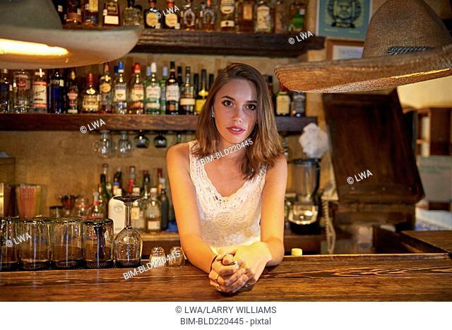 Bartender leaning on bar in restaurant