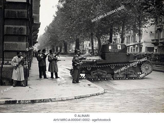 Album Esercito Sud e Partigiani: Armed civilians on the street in Milan in the shelter of a tank type M13 / 40 captured the enemy, shot 1945 by Publifoto