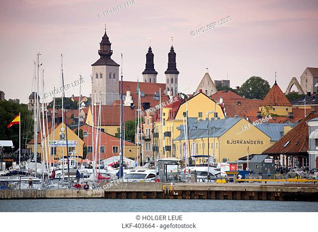 Sailing boats at marina, colourful buildings and Domskyrkan cathedral at dusk, Visby, Gotland, Sweden, Europe