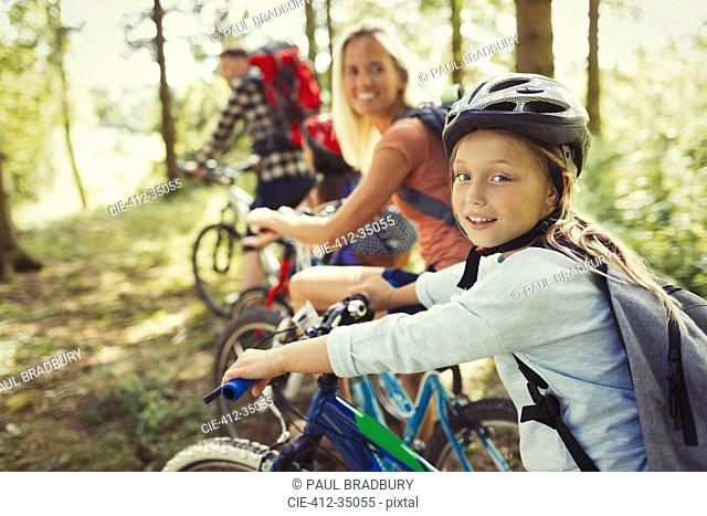 Portrait mother and daughter mountain biking in woods