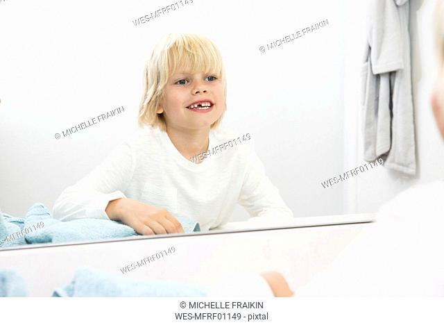 Smiling boy with teeth gap looking in bathroom mirror